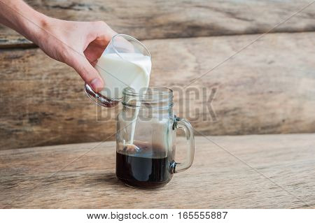 The Glass Of Black Coffee And A Glass Of Milk. Mixing Coffee And Milk