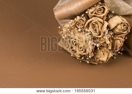 Dried wedding bouquet of roses on brown background.