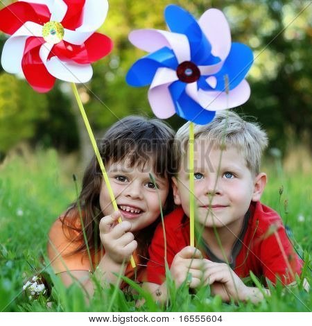 Happy kids with pinwheels on grass