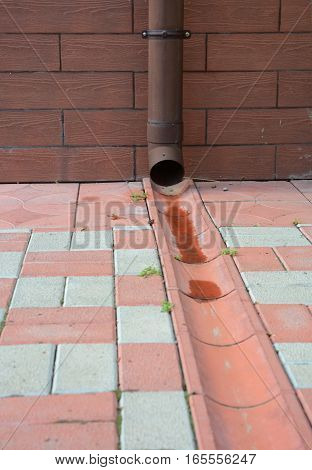 Rain gutter downspout pipe for roof runoff with open water drainage in the pavement.