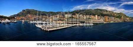 Monte Carlo Monaco - December 08 2009: luxury yachts or ships at moorage in sea city port pier along mountain coast on sunny day on blue sky background
