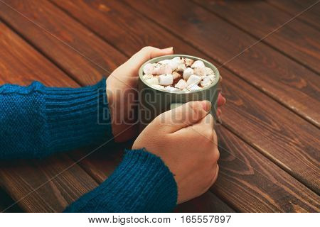 Mug of cocoa or hot chocolate with marshmallows and cinnamon in female hands on wooden rustic table. Coffee, cocoa, cinnamon