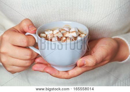 Young woman wrapped in a white knitted blanket and holding mug with hot coffee or cocoa and marshmallows. Female hands holding green cup of hot cocoa. Christmas morning. New Year. Cozy winter. Toned image.