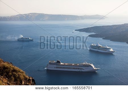 Three cruise ships in the caldera Santorini island Greece. View from the Oia village. Wide angle