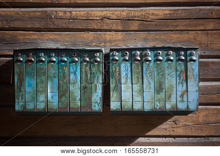 Vintage rusted metal mailboxes on the wooden wall. Photo is made using vintage Helios Lens so it has some blurry effect.