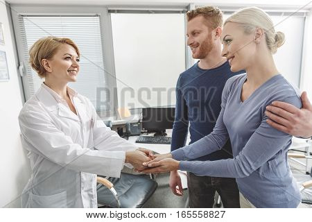 Smiling gynecologist is standing beside patients. She shaking hands with thankful woman