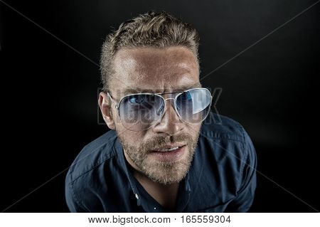 young handsome man or sexy guy with trendy hair and beard on amazed face in blue fashionable glasses and shirt in studio on black background