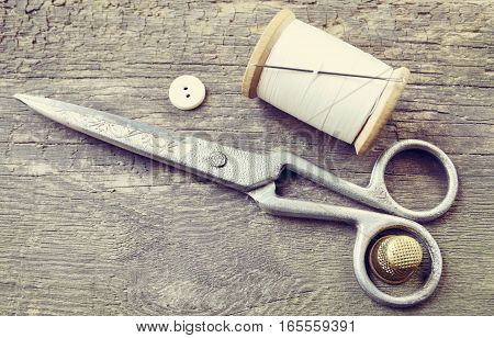 Vintage Background with sewing tools.Sewing kit. Scissors,button,bobbin with thread,needle and thimble on the old wooden background.