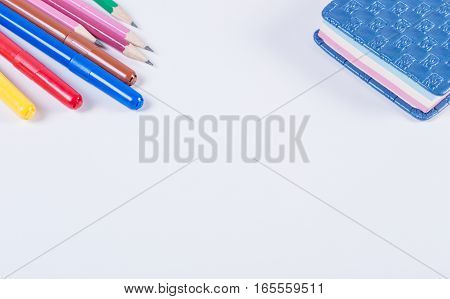 Lying on a white background with school supplies.