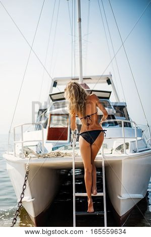 Beautiful bikini woman down the stairs on white yacht in the sea