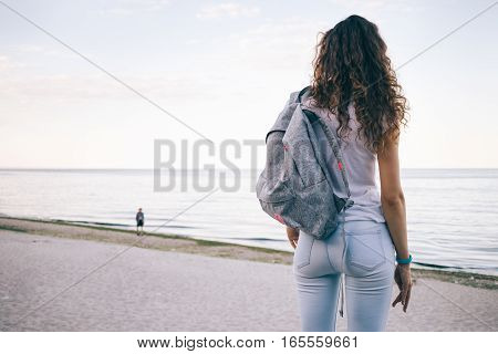 Young Sporty Woman With Curly Hair, Wearing Jeans And A Backpack Standing On The Beach And Looking A