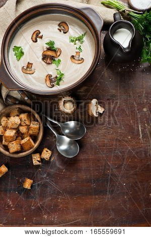 Top view of mushroom cream soup with croutons and fresh parsley on a old wooden table with copy space.