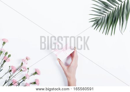 Holiday Concept: Female Hand Puts On The White Table Box Gift