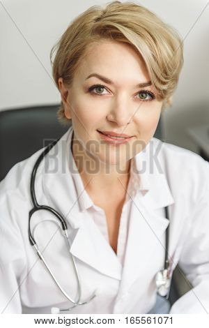 Assured doctor is looking at camera with smile and confidence. Modern stethoscope on her shoulders