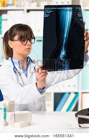 Female Doctor Looking At Patients X-ray
