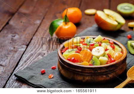 Fresh winter fruit salad on wood background.
