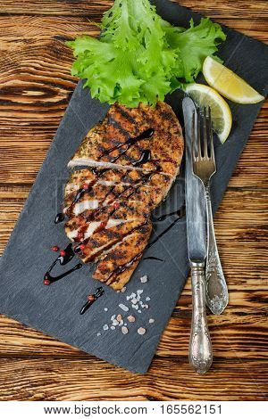 Grilled Chicken Fillet With Spices, Sliced And Served With Lemon And Salad Leaves. Selective Focus