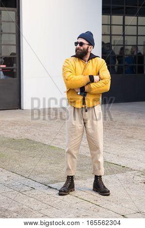 MILAN ITALY - JANUARY 15: Fashionable man poses outside Damir Doma fashion show building during Milan Men's Fashion Week on JANUARY 15 2017 in Milan.