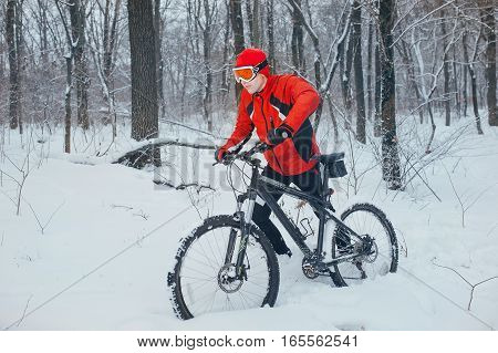 Extreme cyclist rides in the winter snowy forest