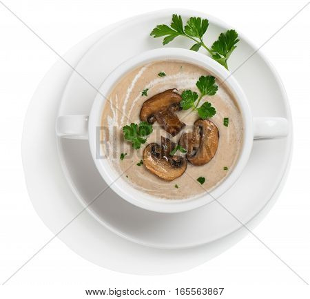 Top view of mushroom cream soup decorated with sliced champignons and parsley in a white ceramic bowl. Isolated on white background.