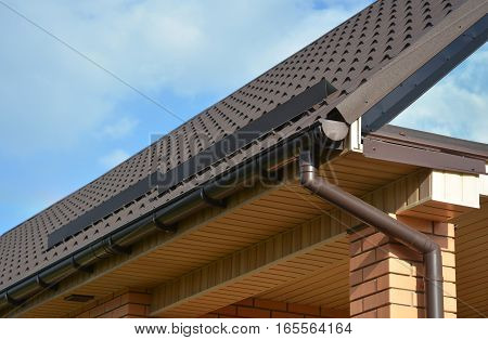 Building Modern House Construction with metal roof corner rain gutter system and roof protection from snow board snow bar (Snow guard). Roof Snow Guards: Building Materials & Supplies