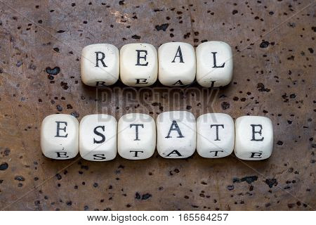 Real Estate Text On Wooden Cubes On A Brown Cork Background
