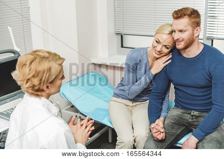 Joyful woman is sitting near her boyfriend with smile on her face. They are in front of medical advisor