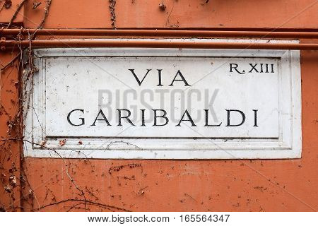 Via Garibaldi, street plate on a wall of old house in Trastevere district, Rome, Italy