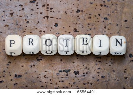 Protein word on wooden cubes on a brown cork background