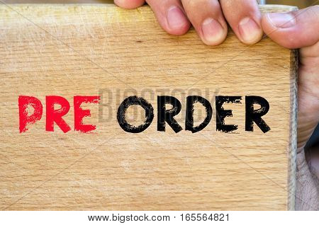 Human hand over wooden background and pre order text concept