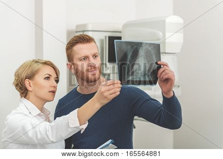 Concentrated medical advisor is standing beside serious patient. They looking at x-ray