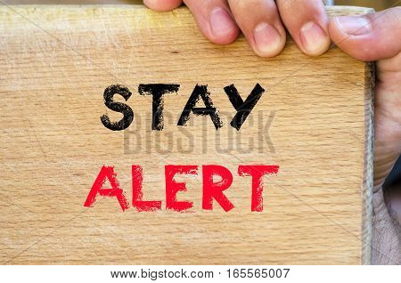 Human hand over wooden background and stay alert text concept