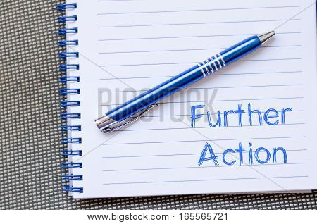 Further action text concept write on notebook