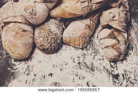 Baking and cooking concept background. Border of different bread sorts, wrapped in craft paper top view with copy space on wooden table, sprinkled with flour.