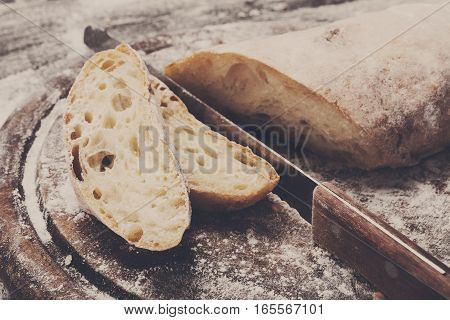 Baking and cooking concept background. Cut white bread loaf with knife on rustic wood sprinkled with flour. Stained dirty surface of table.
