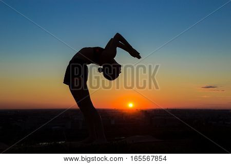 Silhouette of sporty woman practicing yoga in the park at sunset - drop back, wheel pose. Sunset light, sun lens flares, golden hour. Freedom, health and yoga concept