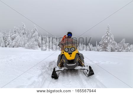 Athlete is resting on a snowmobile during a walk in the mountains of the Southern Urals.