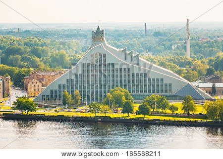 Riga, Latvia. Aerial View Of National Library Building, Named Castle of Light Or Gaismas Pils. Famous Landmark On Daugava Left Bank, Summer Green Landscape With Skyline Background