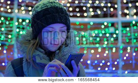 Young pretty woman using smartphone in the city at night. Christmas, technology and holiday concept