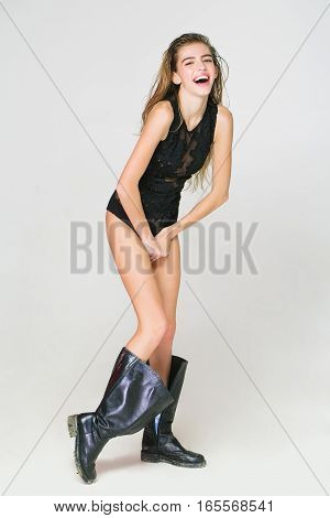 young pretty smiling woman or cute sexy girl with long wet hair in fashionable black lace bodysuit and dirty boots poses on white background