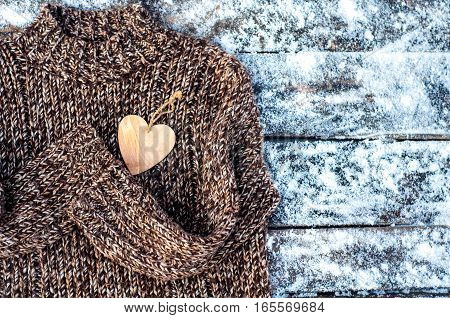 Men's Sweater with decorative heart on a wooden background