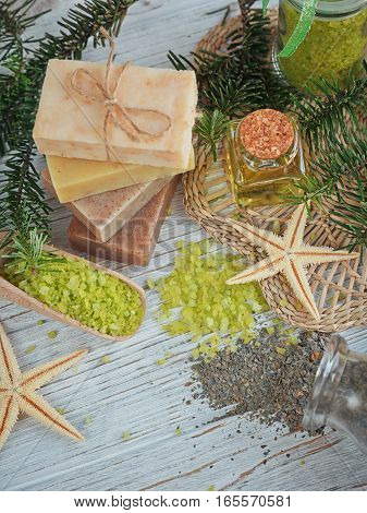 Natural sea salt and handmade soap with branch of pine and seaweed on white wooden background. SPA concept.