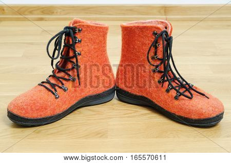 The pair of orange boots is felt on the wooden floor.