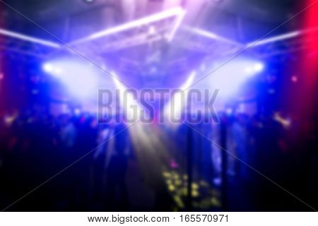 Lights in the club at midnight. Crowd of people at party. Motion blurred picture.