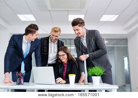 Team of business people work at a desk, smiling, laughing in modern office.