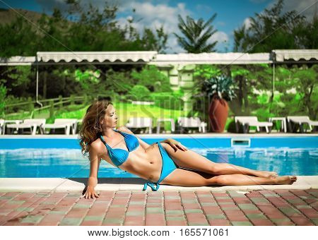 Beautiful slim sexy woman wearing blue bikini relax near outdoor water pool on resort