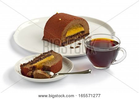 Piece of Cake-Buche on a plate and cup of tea over white background