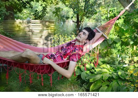 man lying in a hammock in the green garden