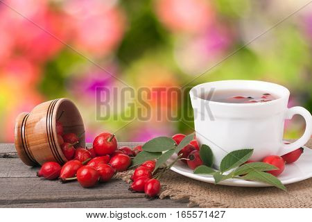 Tea from the hips on the wooden table with a blurred background.