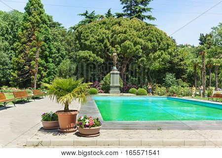 Russia, Crimea, Yalta, Nikita Botanical garden June 09.2016: Pool and a sculpture of Flora